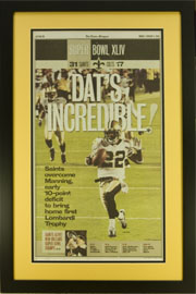 "Newspaper Frame. New Orleans Saints win SuperBowl LXIV. Frame #203, Outer Mat Chamois Gold, Inner Mat Black. Matte Black 1 3/16"". Price $115.95 as configured"